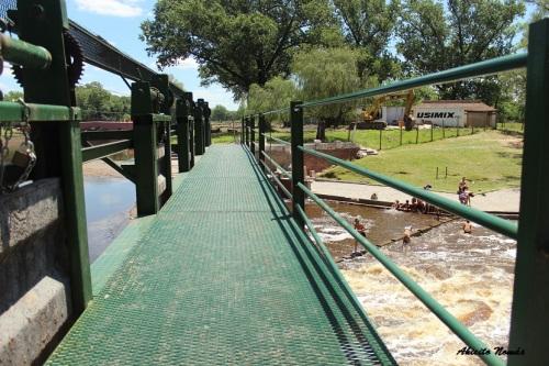 Desde la pasarela de las compuertas se observa como los niños juegan en el río.